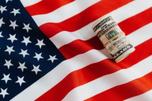 Rolled up money on top of American flag.