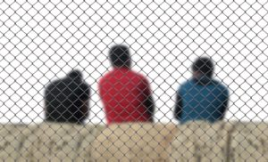 Three people behind a fence.